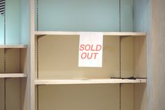 Sold out sign on empty shelves stock images