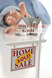 Sold Real Estate Sign in Front, Reaching for House Stock Image