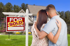 Sold For Sale Sign with Military Couple Looking at House Stock Photography