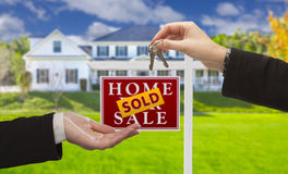 Sold Sign and Agent Handing Over Keys to New Home Royalty Free Stock Photography
