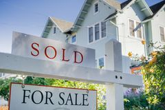 Sold sign in front of a house in a residential neighborhood. Sold sign in front of a generic house in a residential neighborhood, California stock image