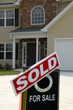 SOLD Sign in Front of New Home. A realtor SOLD Sign in Front of Beautiful New Home Stock Image