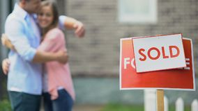Sold sign with hugging young couple on background, private property, relocation stock footage