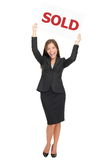 Sold sign real estate agent - Happy realtor. Realtor showing sold sign happy and excited. Smiling joyful Asian / Caucasian real estate agent woman celebrating a royalty free stock image