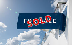 SOLD sign. Sold text sign with blue, white and red colors. Sky background stock images