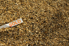 Sold !. A sold tag in a bed of stones royalty free stock photography