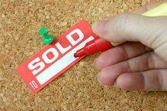 Sold To. Sign on cork board with hand holding red pen ready to write Stock Images