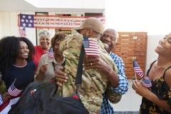 Soldado afro-americano milenar que retorna em casa a sua família, abraçando o avô, vista traseira imagens de stock royalty free