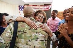 Soldado afroamericano milenario que vuelve a casa a su familia, abrazando a la abuela, visión trasera foto de archivo libre de regalías