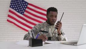 Soldado afroamericano que usa el sistema del ordenador y de radio portátil almacen de video