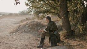 Soldado alemán cansado que se sienta en la maleta en la sombra del árbol almacen de metraje de vídeo