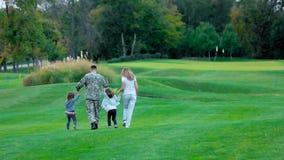 Soldado americano com seu familiy feliz tendo o divertimento no prado do parque filme