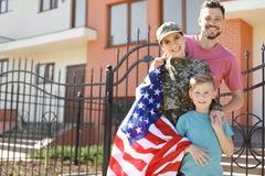 Soldado americano con su familia, al aire libre Servicio militar foto de archivo