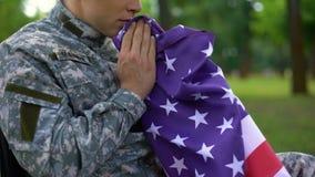 Soldado americano herido con la bandera nacional en manos que piensa en la guerra, memorias metrajes
