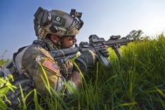 Soldado americano que aponta seu rifle no fundo do céu azul Fotografia de Stock Royalty Free