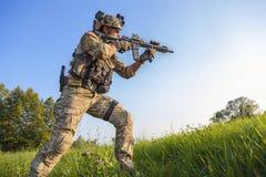 Soldado americano que aponta seu rifle no fundo do céu azul Fotos de Stock Royalty Free
