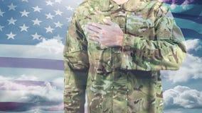 Soldado americano que toma un compromiso y una bandera americana que se sacuden en el fondo almacen de video