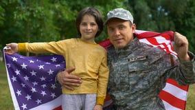 Soldado americano y muchacho que sostienen la bandera nacional, mirando la cámara, orgullo del país almacen de metraje de vídeo