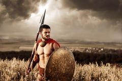 Soldado atlético en la capa roja que lleva como espartano Fotos de archivo