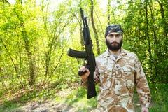 Soldado barbudo con un rifle en el bosque Imágenes de archivo libres de regalías