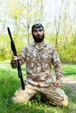 Soldado barbudo con un rifle en el bosque Foto de archivo libre de regalías