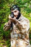 Soldado barbudo con un rifle en el bosque Fotos de archivo libres de regalías