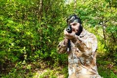 Soldado barbudo con un rifle en el bosque Foto de archivo