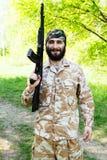 Soldado barbudo con un rifle en el bosque Imagenes de archivo