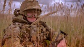 Soldado caucásico auténtico persistente en sentarse que lleva del casco y del camuflaje en el alto degrasse aislado y la mirada almacen de metraje de vídeo