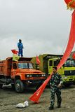 soldado chinês que anda perto por alguns caminhões resistentes com um trabalhador na parte superior que acena a bandeira vermelha imagem de stock