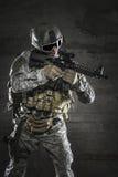 Soldado com a máscara que aponta um rifle imagem de stock