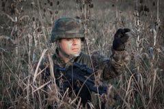 Soldado con el casco militar y arma camuflado en la acción Fotografía de archivo