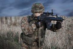Soldado con el casco militar y arma en la acción Fotos de archivo libres de regalías