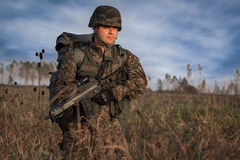 Soldado con el casco militar y arma en la acción Imagen de archivo