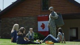 Soldado con la familia en patio trasero verde almacen de metraje de vídeo