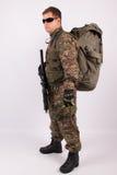 Soldado con la mochila y el arma en el fondo blanco Foto de archivo libre de regalías