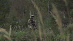 Soldado con un arma en su mano en una colina en un bosque metrajes