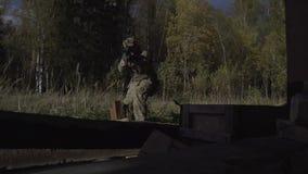 Soldado con un arma en un campo cerca de los fuegos del edificio almacen de metraje de vídeo