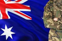 Soldado cruzado de las armas con la bandera que agita nacional en el fondo - tema militar XXX fotos de archivo