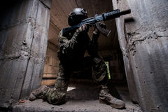 Soldado das forças especiais que aponta um rifle na sala escura Imagem de Stock