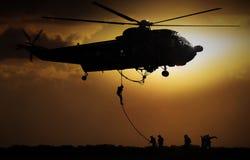 Soldado de caída del helicóptero durante puesta del sol foto de archivo