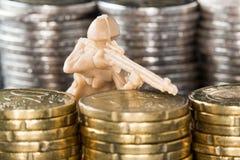 Soldado de juguete entre pilas de monedas Foto de archivo libre de regalías