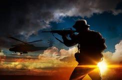 Soldado de la silueta en la puesta del sol Imagen de archivo
