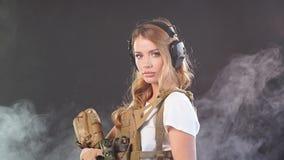 Soldado de sexo femenino en rifle de francotirador militar de la tenencia del uniforme y del casquillo del camuflaje C?mara lenta metrajes