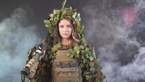 Soldado de sexo femenino pesadamente armado en el casco de la batalla que sostiene el rifle de asalto almacen de video