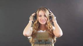 Soldado de sexo femenino rubio vestido en portador y warbelt de la placa Mujeres, concepto del ej?rcito almacen de video