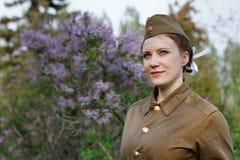 Soldado de sexo femenino soviético bajo la forma de Segunda Guerra Mundial contra la perspectiva de la lila Foto de archivo