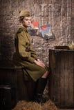 Soldado de sexo femenino soviético en el uniforme de la Segunda Guerra Mundial en el cobertizo Imagenes de archivo