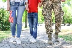 Soldado de sexo masculino con la familia al aire libre Servicio militar fotos de archivo