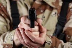 Soldado de sexo masculino que señala su arma adelante Imagen de archivo libre de regalías